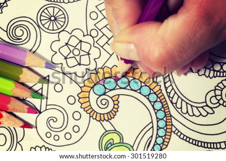 An image of a new trendy thing called adults coloring book with a vintage twist. In this image a person is coloring an illustrative and detailed pattern for stress relieve for adults. - stock photo