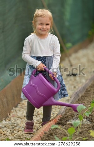 An image of a nice little girl in garden with flower - stock photo