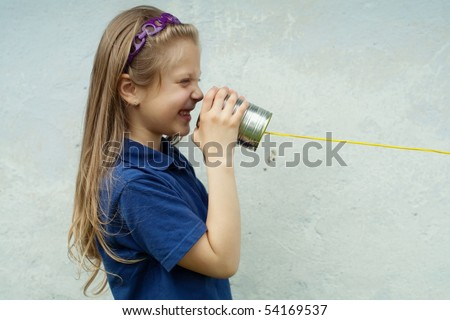 An image of a nice little girl with a toy-telephone - stock photo