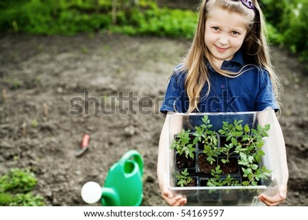 An image of a nice little girl with seedlings - stock photo
