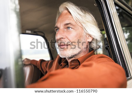 An image of a nice man in his historic car - stock photo