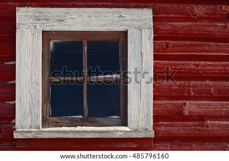 An image of a old white window on a bright red building.