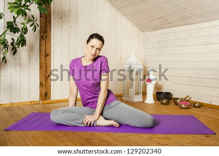 An image of a pretty woman doing yoga at home