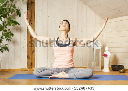 An image of a pretty woman doing yoga at home -