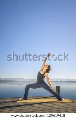 An image of a pretty woman doing yoga at the lake - Parivrtta Parshvakonasana - stock photo