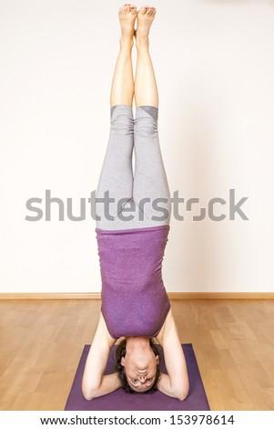 An image of a pretty woman doing yoga - Salamba Shirshasana Head Stand - stock photo