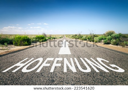 An image of a road to the horizon with text hope in german language - stock photo