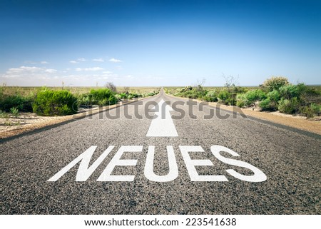 An image of a road to the horizon with text new in german language - stock photo