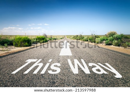 An image of a road to the horizon with text this way - stock photo