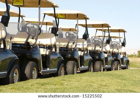 An image of a row of golf carts on a course - stock photo