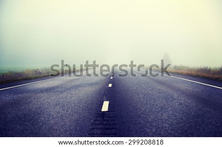 An image of a silent asphalt road on a very foggy morning. Image taken during sunrise and from a low point of view. Image has a vintage effect.