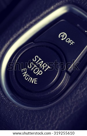 An image of a start and stop button in a modern car. Also a smaller button for switching the automatic feature off is above the button. Image has a vintage effect applied.