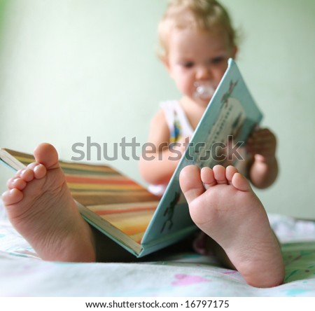 An image of a toddler reading a book. Foots closeup - stock photo