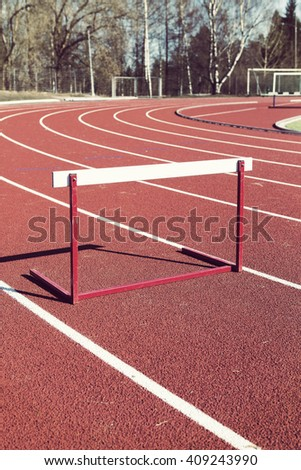 An image of a training hurdle in the sunshine. Image taken outdoor in the training field. The hurdle obstacle is a bit lower than normal. Image has a vintage effect applied.
