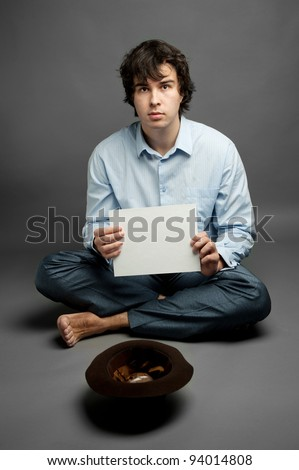 An image of a young beggar with hat - stock photo