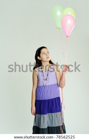 An image of a young girl with three balloons