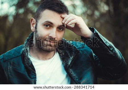 An image of a young man with a black leather jacket - stock photo