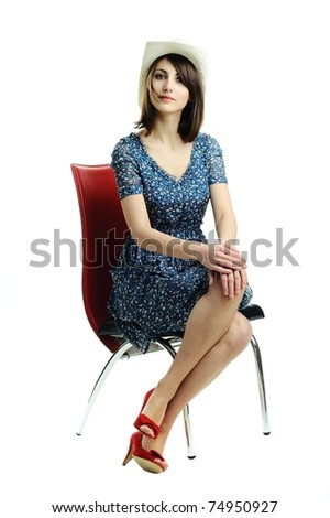 An image of a young woman in a hat sitting on a chair - stock photo