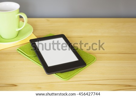 An image of an ebook reader on a wooden table - stock photo