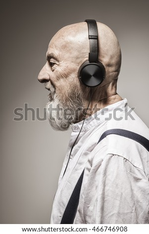 An image of an elderly bald head man listening to music with headphones