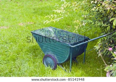 An image of an old green wheelbarrow