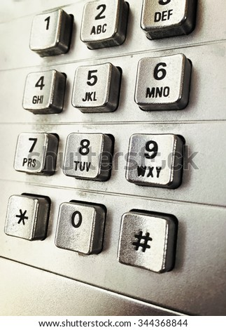 An image of an old telephone which worked with coins. Number buttons are metallic. Image has a vintage effect applied. - stock photo