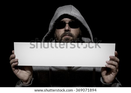 An image of an unrecognizable man in the dark with a white board - stock photo