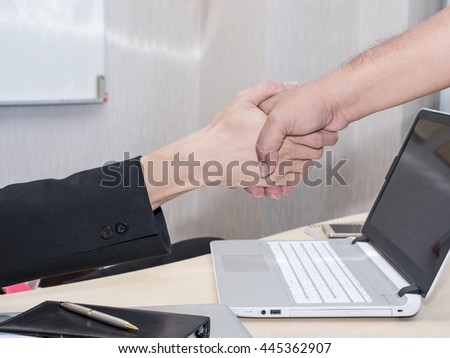 An Image of Asian Business People Handshaking with Office Background, Atmosphere, and Environment for Successful Cooperation Concept.