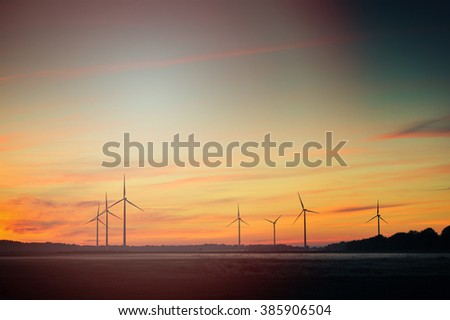 An image of beautiful landscape image with windturbine farm at the sunset