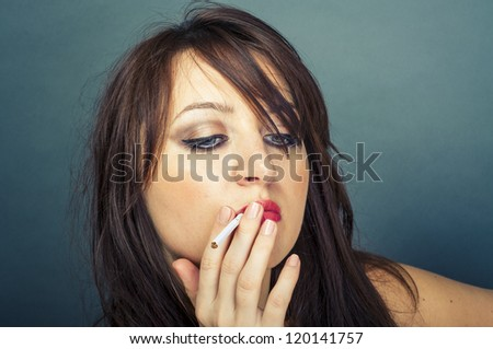 An image of beautiful woman smokes a cigarette