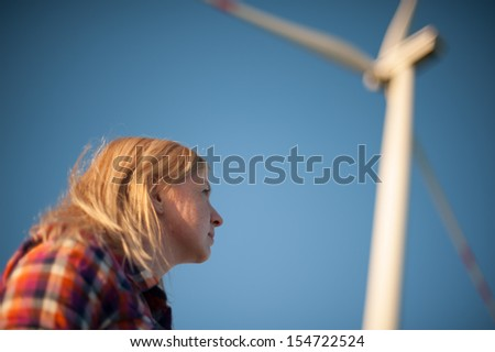 An image of blonde girl and windturbine in the background - stock photo