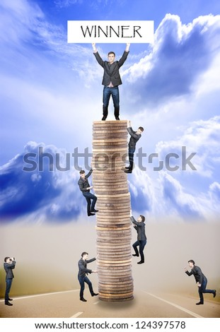 An image of businessmens climbing to tower made of coins