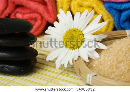 An image of chamomile flower, salt and stones for spa