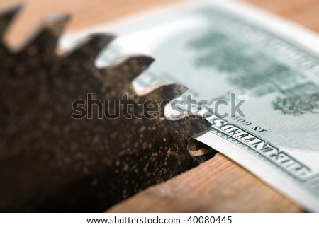An image of dollar and circular saw - stock photo