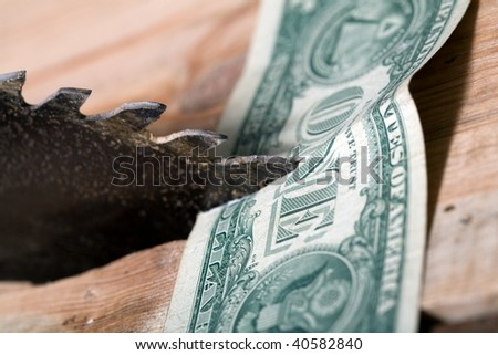 An image of dollar under the saw - stock photo