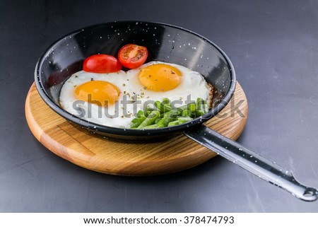 an image of Fried egg on a pan served with tomato and asparagus