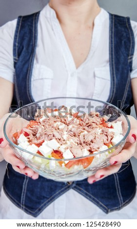 An image of girl holding tuna salad in salad bowl