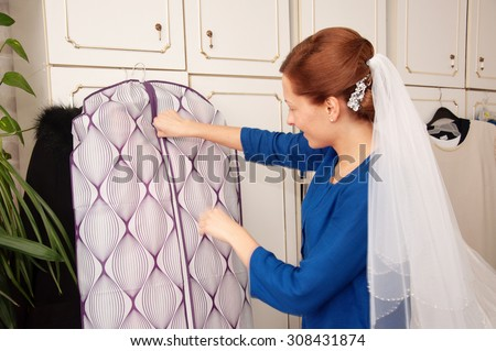an image of helping the bride to put her wedding dress on