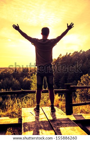 An image of man with open hands at the edge of woods - stock photo