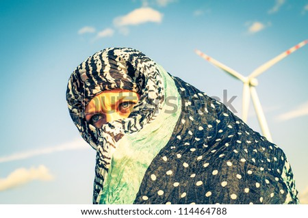 An image of muslim girl and windturbine in the background - stock photo