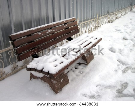 an image of snow covered empty bench - stock photo
