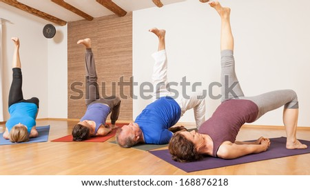 An image of some people doing yoga exercises - Eka Pada Setu Bandha Sarvangasana