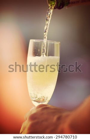 An image of someone pouring champagne to a glass in the summer and outdoors. Image has a vintage effect.