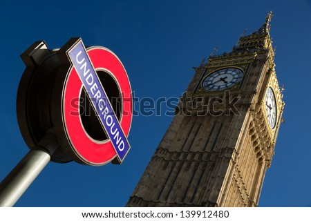 An image of the palace of Westminster with a color image of the underground sign in the foreground - stock photo
