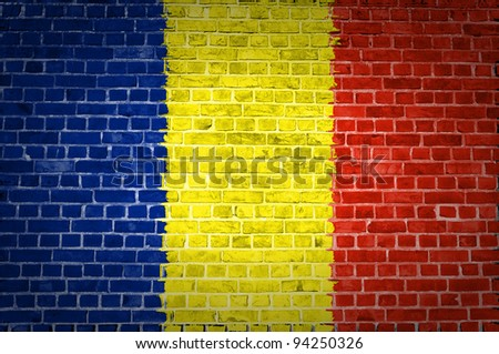 An image of the Romania flag painted on a brick wall in an urban location