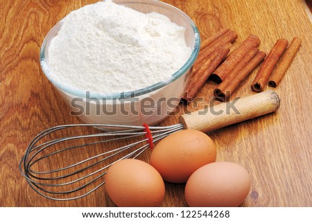 An image of three eggs with flour and cinnamon on a wooden table