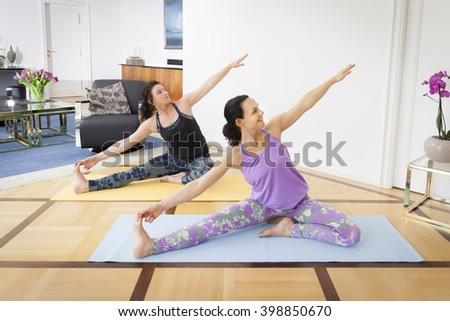 An image of two women doing yoga in the living room at home - stock photo