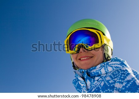 An image with a portrait of a female snowboarder wearing a helmet and glasses with reflection of snow-capped Alps in Grindelwald, Swiss - stock photo