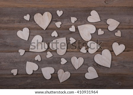 An image with different sized wooden hearts on a wooden background.