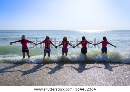 An image with lens flare effect of 5 asian girls standing with hand in hand on the beach which have blue sea and blue sky as background